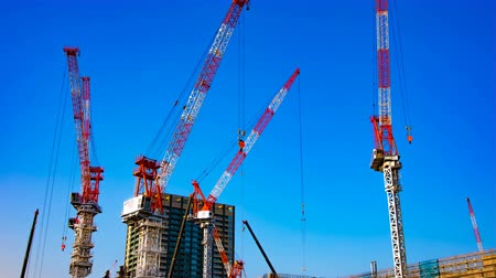 high rises : A time lapse of moving cranes at the under construction in Tokyo wide shot panning Stock Footage