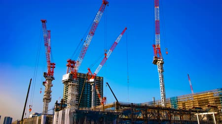 high rises : A time lapse of moving cranes at the under construction in Tokyo wide shot tilt