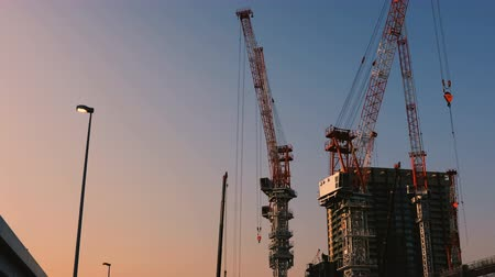 high rises : Cranes at the under construction in Tokyo wide shot at dusk