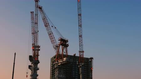 em desenvolvimento : Cranes at the under construction in Tokyo wide shot at dusk