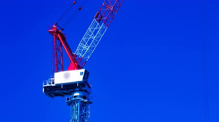 construction crane : A time lapse of moving cranes behind the blue sky at the under construction in Tokyo