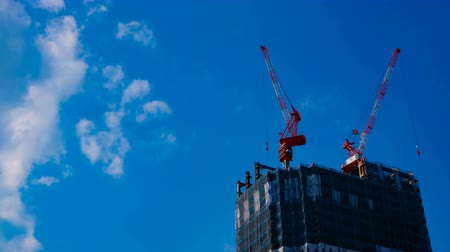 gelişme : A timelapse of cranes at the under construction behind the blue sky in Tokyo