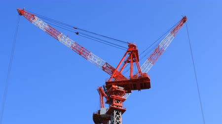 строительные леса : Moving cranes at the under construction behind the blue sky in Tokyo