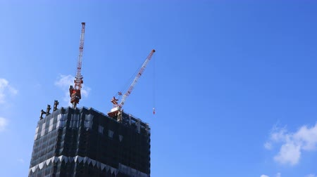em desenvolvimento : Moving cranes at the under construction behind the blue sky in Tokyo