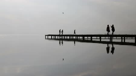 mistério : Silhouette of young people and couple walking down the mysterious lake on the pier