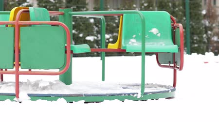 Colourful merry go round on a snowy playground