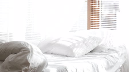 White bed close to the jalousie window with white moving curtains on the draft.Sliding movement