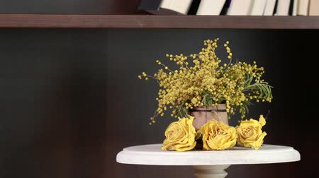 Dehydrated bud of yellow roses and mimosa on a cake wooden stand