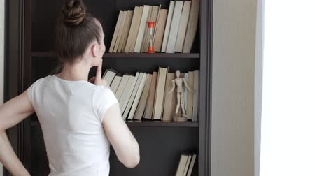 Home library in the cupboard. Young lady is choosing a book. Vídeos