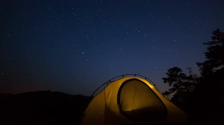 atividades : Illuminated tent at night under moving stars. Time lapse Stock Footage