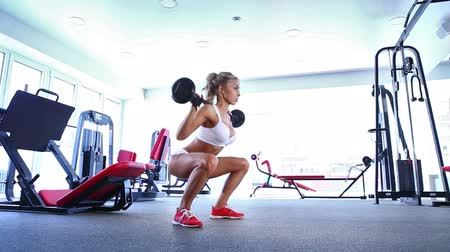 сильный : Sportive young woman doing exercise with barbell in the gym Стоковые видеозаписи