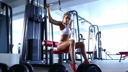 musculação : Attractive young woman working out on weight-lifting training machine