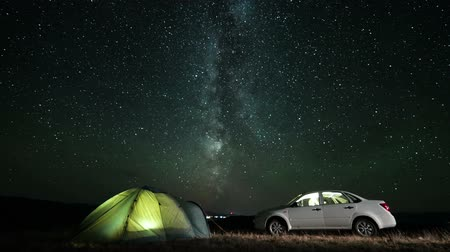 atividades : Illuminated tent near car at night under moving stars. Slider time lapse