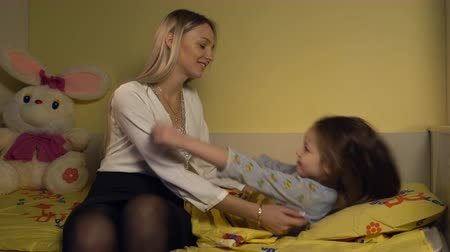 капелька : Mother kissing and hugging her daughter on the bed. Стоковые видеозаписи