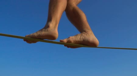 tightrope : Legs of Man Walking on The Rope at the Extreme sports festival. Slackline walk Stock Footage