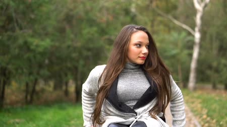 tek başına : Attractive girl on a wheelchair walking in the autumn park. Disabled leisure Stok Video
