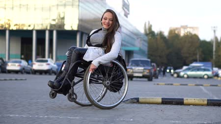 rokkant : Attractive disabled girl dancing on a wheelchair at the parking. Autumn leisure Stock mozgókép