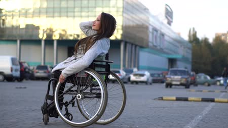 инвалидность : Attractive disabled girl dancing on a wheelchair at the parking. Autumn leisure Стоковые видеозаписи