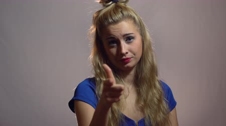 Beautiful Sexy Blonde Girl in Blue Dress is Point on You in Studio with light Background. Motivation video