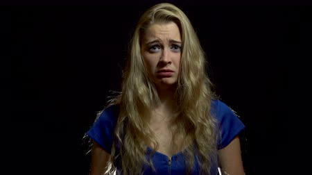 Beautiful Sexy Blonde Girl in Blue Dress is Upset and Vulnerable in Studio with Black Background.