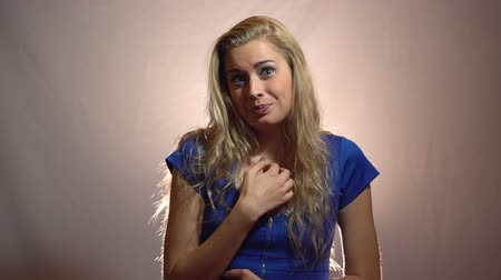 Beautiful Emotional Blonde Girl in Blue Dress feels guilty in Studio with light Background.
