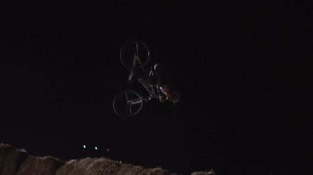 backflip : 20AUG2017, Odessa, Ukraine. Slow Motion video of extreme Athlete man Doing an amazing whip trick on the MTB Bmx Bike While Dirtjumping at Night at the Festival Extreme Ukraine 2017 Stock Footage
