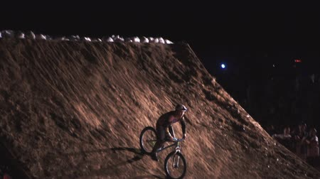 20AUG2017, Odessa, Ukraine. Slow Motion video of extreme Athlete man Doing an amazing trick on the MTB Bmx Bike While Dirtjumping at Night at the Festival Extreme Ukraine 2017 Стоковые видеозаписи