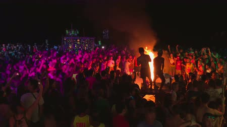 teljes test : KOH PHANGAN,THAILAND - NOVEMBER 16, 2016 : Unidentified girls and boys dancing the Full Moon party in island Koh Phangan. The event now attracts anywhere from 40,000 party-goers on a normal month Stock mozgókép