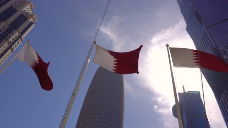 cercar : DOHA, QATAR - FEBRUARY 12, 2018: Three National Flags are Fluttering in Modern City. Skyscrappers Surround Stock Footage