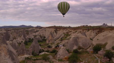 TURKEY, GOGEME - MAY 20. Huge Air Balloon Flying over the Cappadocia Rocks in the Cloudy Sky.