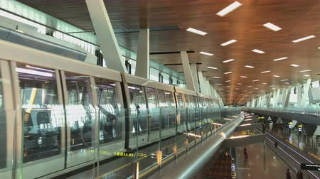 DOHA, QATAR - 23 MAR, 2018 : Airport Train Riding Between Terminals and Passengers walk through the Modern Departure hall of Hamad International Airport in Doha, Qatar.