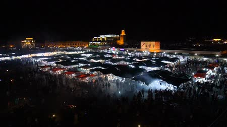 fas : MOROCCO - MARRAKECH JAN 2019: Night view of Djemaa el Fna, a square and market place in Marrakech medina quarter Stok Video