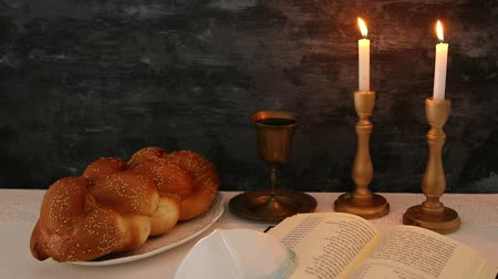 jewish prayer : shabbat footage. challah bread, shabbat wine and candles on the table