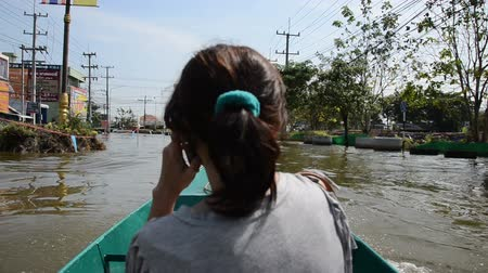 evacuated : NAKHON PATHOM, THAILAND - NOV 15: unidentified woman use boat as transportation on Phutthamonthon Sai 4 road  during the worst flooding crisis  on November  15, 2011 in Nakhon Pathom, Thailand Stock Footage