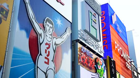 osaka : OSAKA, JAPAN - APRIL 30 : the famous Glico running man billboard and other advertisement sign in Dotonbori district on April 30, 2017 in Osaka, Japan. Stock Footage