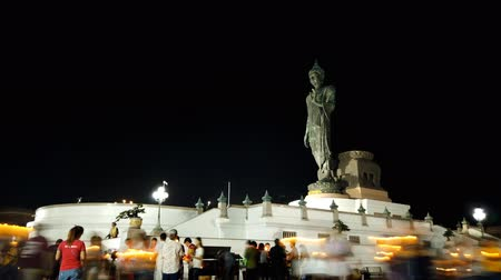 NAKHON PATHOM, THAILAND - MAY 18 : Motion time lapse of people walking past the side of buddha in Visakha Bucha Day at Buddhist park in Nakhon Pathom , Thailand on May 18, 2019