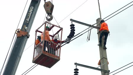gaiola : NAKHON PATHOM, THAILAND SEPTEMBER 8 : Unidentified Electrician working at a newly installed utility pole on a lift, connects a new electrical power line at Nakhon Pathom ,Thailand on September 8, 2019 Vídeos