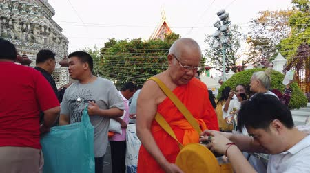 заслуга : BANGKOK THAILAND - JANUARY 1 : Unidentified people make merit with monk at the Temple of Dawn Wat Arun in New year festival on January 1, 2020 in Bangkok, Thailand. Стоковые видеозаписи