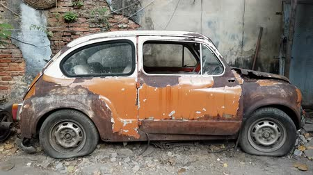 BANGKOK THAILAND - JANUARY 2 : Old vintage abandoned FIAT 600 car park at sidewalk with old red brick wall background is landmark of tourist at Talad Noi street on January 2, 2020 in Bangkok, Thailand