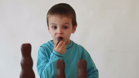 doces : Boy, eating chocolate rabbit, his brother running to him and giving him a kiss on a cheek