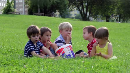 попкорн : Group of adorable kids, eating popcorn in the park, laughing