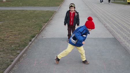 dehet : Cute children, playing on the street, jumping on hopscotch on asphalt