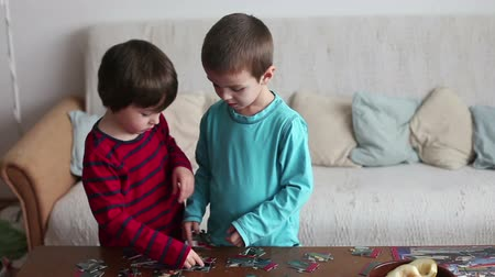 jigsaw : Smart little boys, brothers, making puzzle at home during a weekend day Stock Footage
