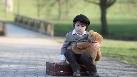 kufr : Cute little toddler boy, with suitcase and teddy bear in the park on sunset, having fun outdoor