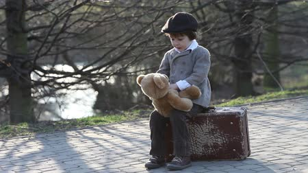 čepice : Cute little toddler boy, with suitcase and teddy bear in the park on sunset, having fun outdoor