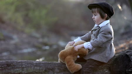 kufr : Cute little toddler boy, with teddy bear in the park on sunset, having fun outdoor