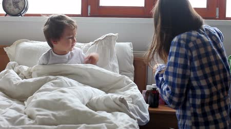 horečka : Sick boy, lying in bed, mother checking his temperature and giving him medicine