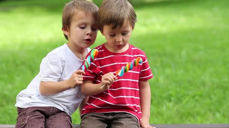 lízat : Adorable boys, licking lollipops outside on a sunny day