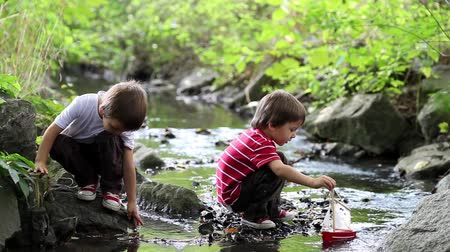 vztahy : Two little brothers playing together with wooden boat by a river on spring or autumn day. Creative leisure with kids