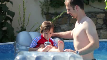 otec : Cute little boy and his father, swimming in a pool in the summer, having fun